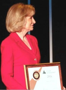 Sandy accepts Junior Achievement's Bronze Leadership Award for her volunteer work with the organization.
