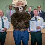 "Sandy proclaims ""Smokey Bear Day"" in Hillsborough County, celebrating Smokey's 70th birthday, and encouraging citizens to be careful when using fire in rural areas. From left are: Commissioner Murman, John Dewolf of the Florida Forest Service, Smokey Bear, Pat Keogh of the FFS, and Mike Facente, Forest Ranger for the FFS."