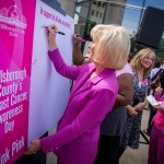 "Sandy signs the ""Think Pink"" poster during Breast Cancer Awareness Day in Hillsborough County"