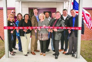 Sandy helps community leaders and county staff cut the ribbon for the new Gardenville Gymnasium in South County. From left are: Tanya Duran, David Ramirez, Jennifer Caskey, Carol Johns, Greg Horwedel, Dexter Barge, Steve Alvarez, Lee Stevens, Rick Valdez and Forest Turbiville.