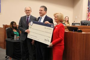 On behalf of Hillsborough County, Commissioner Sandy Murman and County Administrator Mike Merrill accept a check for $113,185.79 from State of Florida Chief Financial Officer Jimmy Patronis. The funds are from the State's Unclaimed Property Fund and are sourced from a variety of accounts in the county's name.