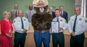 """Sandy proclaims """"Smokey Bear Day"""" in Hillsborough County, celebrating Smokey's 70th birthday, and encouraging citizens to be careful when using fire in rural areas. From left are: Commissioner Murman, John Dewolf of the Florida Forest Service, Smokey Bear, Pat Keogh of the FFS, and Mike Facente, Forest Ranger for the FFS."""