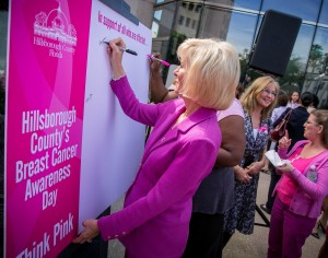 """Sandy signs the """"Think Pink"""" poster during Breast Cancer Awareness Day in Hillsborough County"""